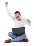 Aufgeregter asiatischer Mann, der Laptop verwendet stockfotografie