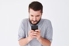 Aufgeregter bärtiger Mann im überprüften Hemd, das auf Smartphone spielt Stockfotografie