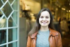 Aufgeregter Brunette, der im Bekleidungsgeschäft und dem Lächeln aufwirft Lizenzfreie Stockfotografie