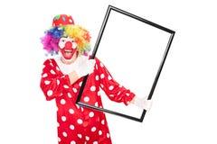 Aufgeregter Clown, der einen großen Bilderrahmen hält Lizenzfreies Stockbild