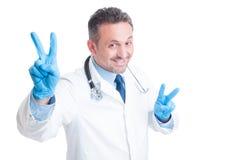Aufgeregter Doktor, der doppelten Frieden zeigen und Sieg gestikulieren Lizenzfreie Stockbilder