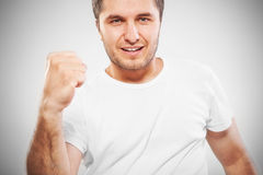 Aufgeregter energischer junger Mann, der Erfolg gestikuliert Lizenzfreie Stockfotos