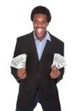 Aufgeregter Geschäftsmann, der Dollarwährung hält Lizenzfreie Stockfotografie