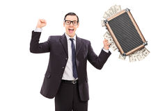 Aufgeregter Geschäftsmann, der eine Tasche voll vom Geld hält Stockbilder
