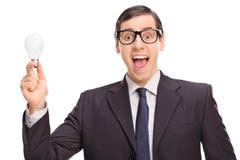 Aufgeregter Geschäftsmann in einem schwarzen Anzug, der eine Glühlampe hält Stockfotos