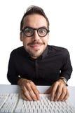 Aufgeregter Geschäftsmann mit Gläsern schreibend auf Tastatur Stockfotos