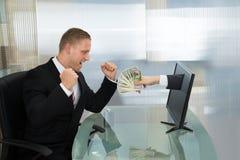 Aufgeregter Geschäftsmann mit dem Geld, das vom Bildschirm herauskommt Stockfotos