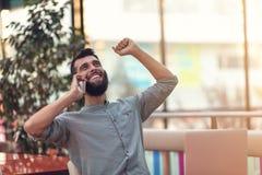 Aufgeregter glücklicher bärtiger Freiberufler, der E-Mail mit Ergebnissen über Sieg im modernen on-line-Wettbewerb sitzt am Lapto stockfotografie