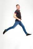 Aufgeregter glücklicher junger springender und laufender Mann Stockfotografie