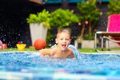 Aufgeregter glücklicher Kinderjunge, der in Pool, Wasserspaß springt Lizenzfreies Stockfoto