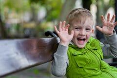 Aufgeregter glücklicher kleiner blonder Junge mit den Händen, die oben Kamera betrachten Stockbilder