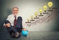 Aufgeregter glücklicher Mann der erfahrenen Führungskraft, der auf einem Boden in seinem Büro mit Sparschwein sitzt Stockfoto
