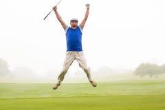 Aufgeregter Golfspieler, der oben springt und an der Kamera lächelt Stockfoto