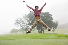 Aufgeregter Golfspieler, der oben springt und an der Kamera lächelt Stockbild
