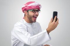 Aufgeregter, hübscher arabischer Mann, der Erfolg ausdrückt lizenzfreie stockfotografie