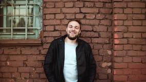 Aufgeregter hübscher europäischer Mann lächelt in Kamera Glücklicher erfolgreicher männlicher Geschäftsmann steht nahe Wand des r stock footage