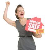 Aufgeregter Hauswirt mit Haus für Verkauf verkaufte Zeichen Stockfoto