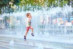 Aufgeregter Junge, der zwischen Wasserstrom im Stadtpark läuft lizenzfreie stockbilder