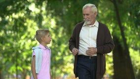 Aufgeregter Junge sagt dem Opa Eindrücken, vertraulichem Gespräch, Freundschaft stock video