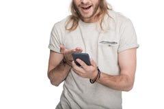 Aufgeregter junger blonder Mann, der Smartphone verwendet Stockfoto