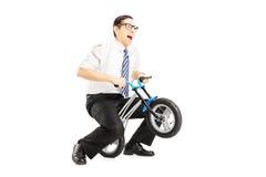 Aufgeregter junger Geschäftsmann, der kleines Fahrrad fährt Stockfotografie