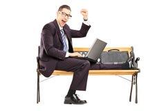 Aufgeregter junger Geschäftsmann mit einem Laptop, der auf einer Bank sitzt Stockbild