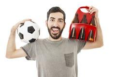 Aufgeregter junger Mann, der Ball und Satz Bier hält Stockfoto