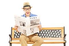 Aufgeregter junger Mann, der eine Zeitung gesetzt auf Bank liest Lizenzfreie Stockbilder