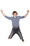 Aufgeregter junger Mann, der in einer Luft springt stockbild