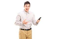 Aufgeregter junger Mann, der in Richtung zu einem Handy zeigt Lizenzfreie Stockbilder