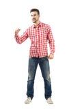 Aufgeregter junger Mann in der zufälligen Kleidung mit der geballten Faust Stockfotografie