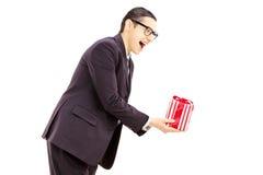 Aufgeregter junger Mann im schwarzen Anzug, der ein Geschenk gibt Stockfoto