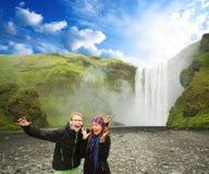 Aufgeregter junger Mann und Frau vor dem Wasserfall lizenzfreie stockbilder
