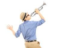 Aufgeregter junger Musiker, der Trompete spielt Stockfoto