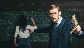Aufgeregter junger Professor mit dem stilvollem Schnurrbart und Bart Buch auf Studenten im Klassenzimmer beim Zeigen von Formel z lizenzfreie stockbilder