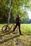 Aufgeregter junger Radfahrer, der in einem Frühlingspark steht Stockbilder