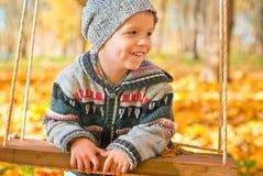 Aufgeregter kleiner Junge auf einem Schwingen im Freien Stockfoto