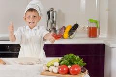 Aufgeregter kleiner Junge, das Pizzahandeln oben kochend Daumen Stockfotos