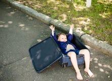 Aufgeregter kleiner Junge, der in einem Kofferzujubeln liegt Lizenzfreie Stockfotografie