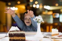 Aufgeregter kleiner Junge, der für eine Scheibe des Kuchens erreicht Stockfotos