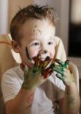 Aufgeregter kleiner Junge, der mit Fingerfarben spielt Stockfotos