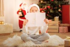 Aufgeregter kleiner Junge, der seine Weihnachtsbaumzeichnung zeigt Lizenzfreie Stockbilder