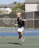 Aufgeregter kleiner Junge, der Tennis spielt Lizenzfreie Stockfotos