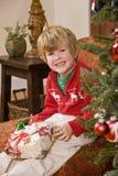 Aufgeregter kleiner Junge mit Geschenk durch Weihnachtsbaum Stockfotografie