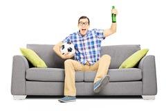 Aufgeregter männlicher Sportfreund mit aufpassendem Sport des Balls und des Bieres Stockfotos