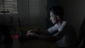 Aufgeregter männlicher Student, der auf seinem Schreibtisch online schreibt und plaudert mit seiner Freundin nachts in einer Dunk stock footage