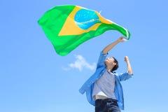 Aufgeregter Mann, der Brasilien-Flagge hält Stockfoto