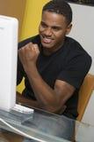 Aufgeregter Mann, der an Computer arbeitet Stockbilder