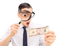 Aufgeregter Mann, der Dollarschein mit Vergrößerungsglas betrachtet Stockfotografie