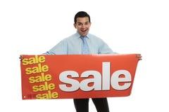 Aufgeregter Mann, der ein Verkaufszeichen anhält lizenzfreies stockfoto